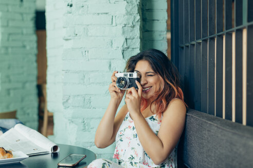 Smiling woman sitting in coffee shop taking pictures with camera - JPF00318
