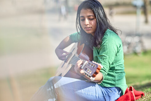 Young woman playing guitar in a park - BEF00019