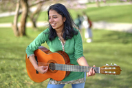 Happy young woman playing guitar in park - BEF00022