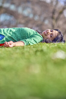 Portrait of happy young woman lying on meadow - BEF00025