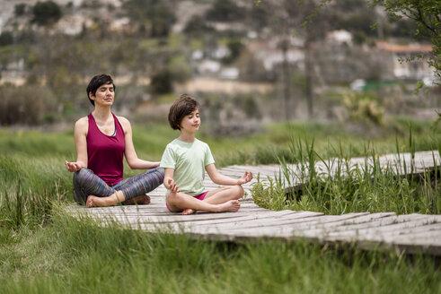 Mother and daughter doing yoga on boardwalk - JSMF00179