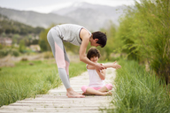Mother explaining yoga position to daughter on boardwalk - JSMF00182