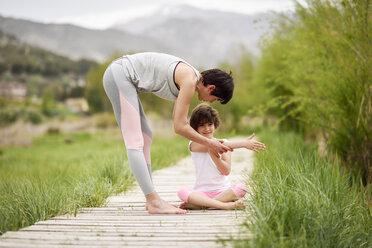 Mother explaining yoga position to daughter on boardwalk - JSMF00182