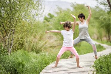 Mother and daughter doing yoga on boardwalk - JSMF00185