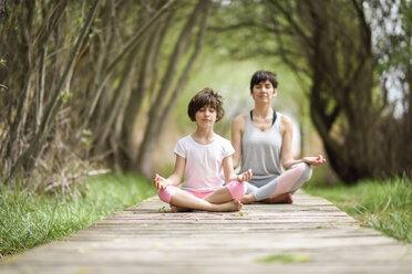 Mother and daughter doing yoga on boardwalk - JSMF00188