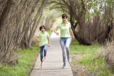 Happy mother and daughter running on boardwalk - JSMF00197