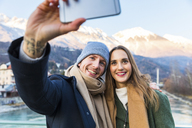 Austria, Innsbruck, portrait of happy young couple taking selfie with smartphone in winter - WPEF00226