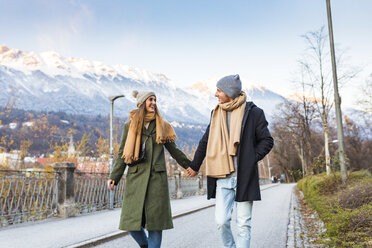 Austria, Innsbruck, happy young couple strolling together hand in hand at winter time - WPEF00232