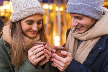 Happy young couple with cups of mulled wine at Christmas market - WPEF00241