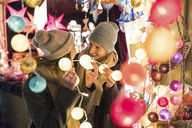 Young couple watching offerings at Christmas market - WPEF00250