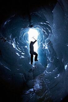 Man exploring glacial cave - CUF00725