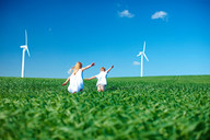Childrens play in field & wind turbines - CUF00752