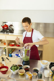 Woman preparing a smoothie in kitchen - EBSF02418