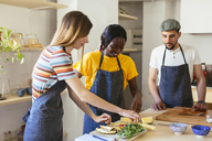 Friends preparing pineapple in kitchen - EBSF02451