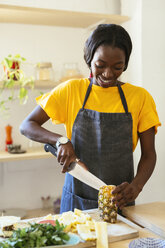 Smiling woman cutting pineapple in kitchen - EBSF02454