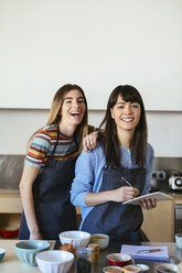 Portrait of two happy women with notebook in kitchen - EBSF02457
