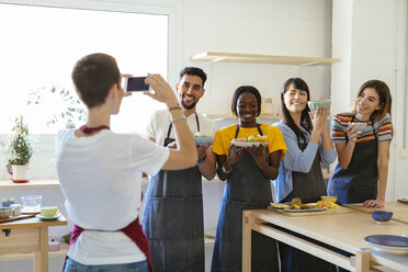 Instructor taking a picture of friends in a cooking workshop - EBSF02463