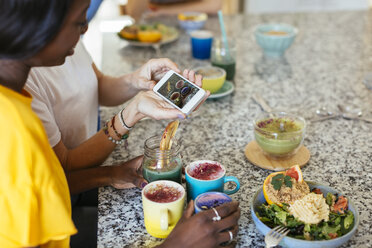 Woman showing smartphone picture in a cooking workshop - EBSF02475