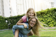 Portrait of happy mother and daughter in urban city garden - SBOF01466