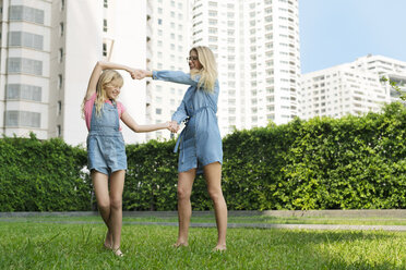 Happy mother and daughter having fun in urban city garden - SBOF01469