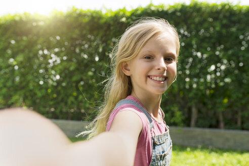 Cute blonde girl taking selfie in garden - SBOF01472