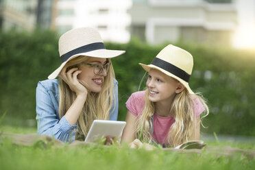 Happy mother and daughter with book and smartphone in urban city garden - SBOF01475