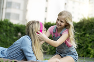 Happy mother and daughter listening to music together in garden - SBOF01478