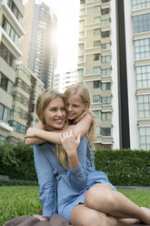 Happy mother and daughter hugging and smiling in urban city garden - SBOF01484