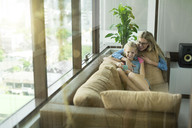Mother and daughter in modern living room on a couch looking at smartphone together - SBOF01490
