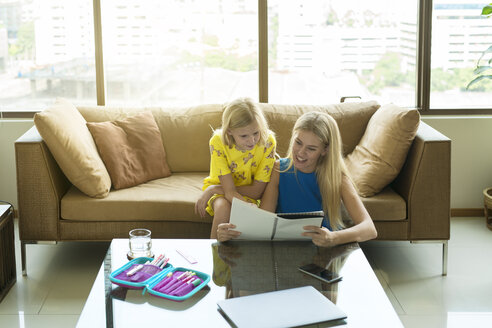 Happy mother and daughter sitting on a couch looking at the girl's homework together - SBOF01496