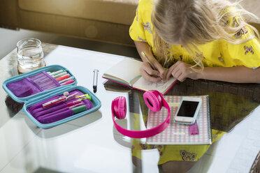 Girl doing her homework writing in booklet on table in living room - SBOF01499