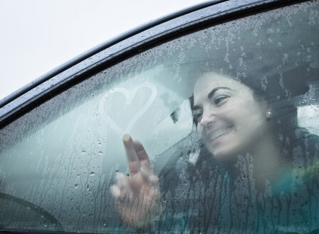 Teenage girl drawing on wet car window - CUF00878