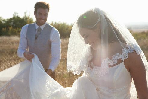 Newlywed groom holding brides dress - CUF00914