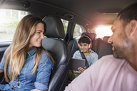 Family on a road trip with boy using tablet - DIGF04137