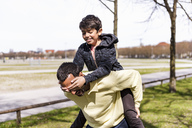 Happy father carrying son piggyback in a park - DIGF04146
