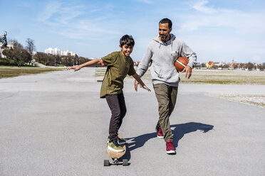 Father and son with longboard and basketball outdoors - DIGF04158