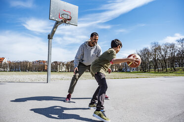 Father and son playing basketball on court outdoors - DIGF04161