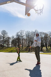 Father and son playing basketball on court outdoors - DIGF04164