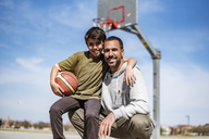 Portrait of happy father and son with basketball outdoors - DIGF04167