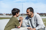 Father and son arm wrestling outdoors - DIGF04176
