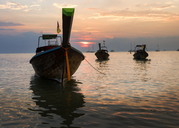 Thailand, Krabi, Railay beach, long-tail boats floating on water at sunset - ALRF01177