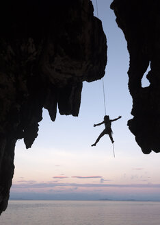 Thailand, Krabi, Lao Liang island, climber abseiling from rock wall above the sea - ALRF01195