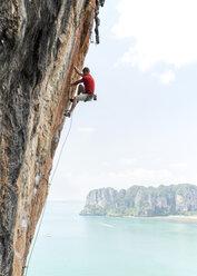 Thailand, Krabi, Thaiwand wall, man climbing in rock wall above the sea - ALRF01201