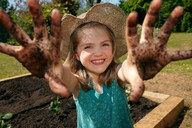 Young girl in garden with muddy hands - CUF00955
