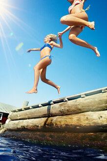 Teenage girls jumping into lake - CUF00988