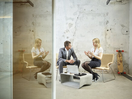 Businessman and businesswoman talking in modern office - CVF00347