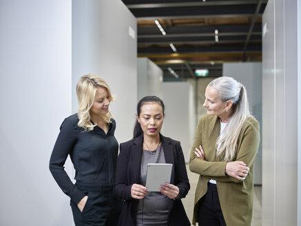 Three businesswomen sharing tablet on office floor - CVF00353