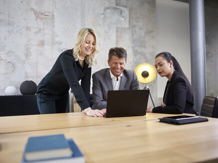 Businessman and two businesswomen sharing laptop in modern office - CVF00356