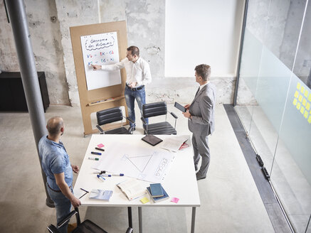 Three businessmen having a meeting with flipchart in conference room - CVF00377