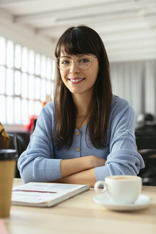 Portrait of smiling young woman with notepad at desk in office - EBSF02501